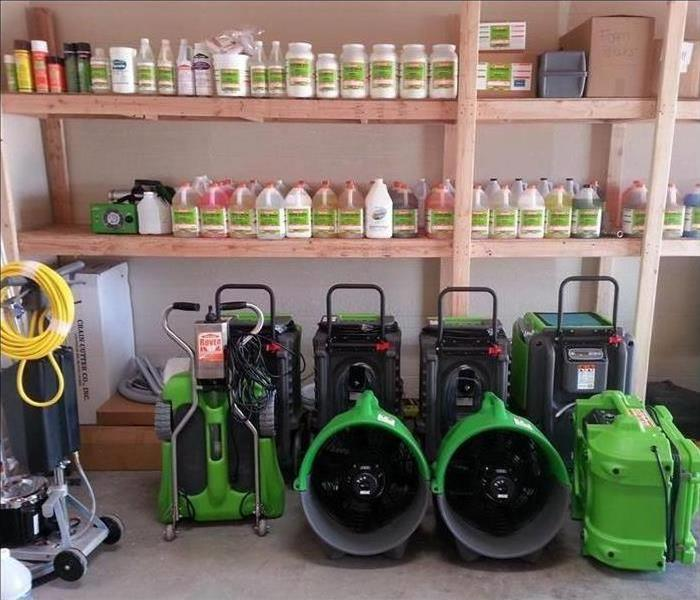 SERVPRO cleaning products on wooden shelves with restoration equipment sitting on the floor