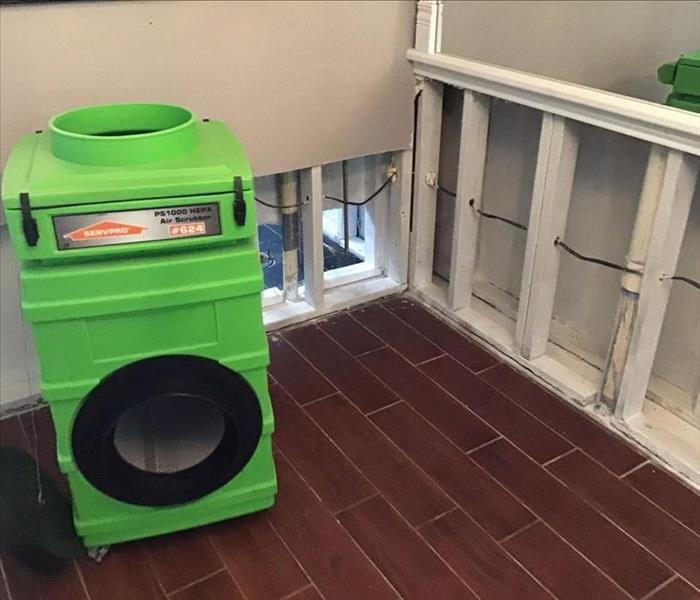 green equipment on top of brown laminate flooring