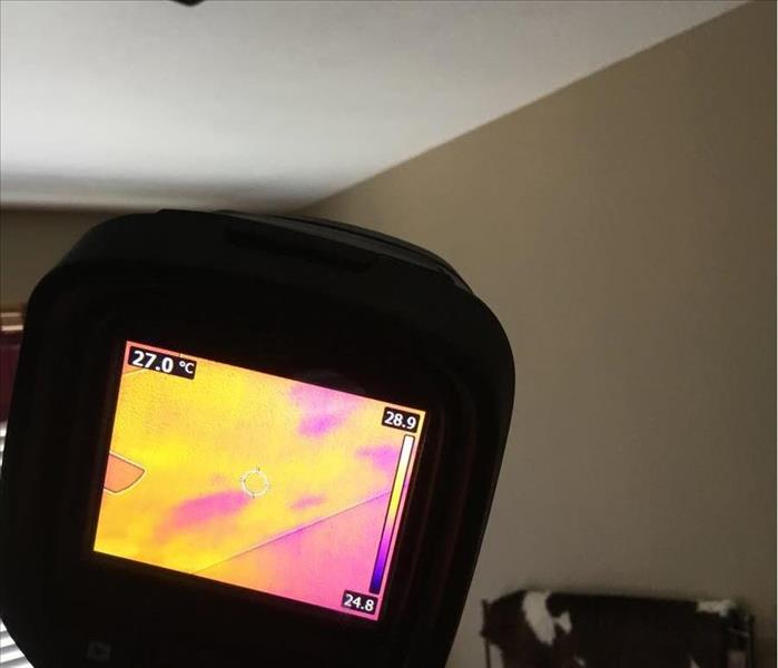 purple and yellow heat patterns of a ceiling shown on a thermal camera