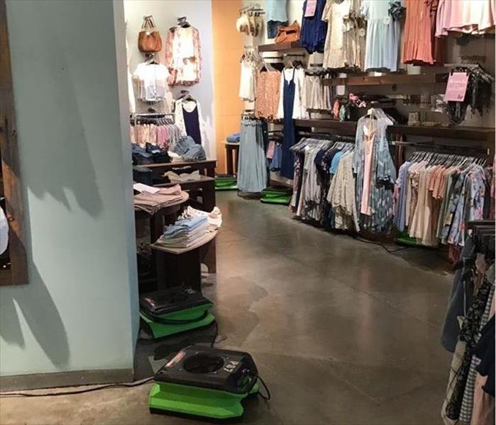 green drying equipment on the floor with clothing hung on displays on the walls